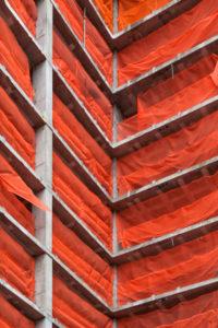Mit roten Netzen verhängter Rohbau